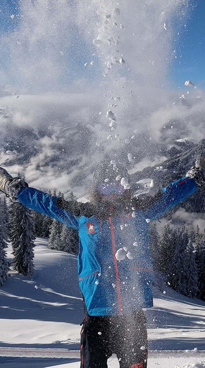 Danski guide i blå jakke kaster med hvid sne i Alperne